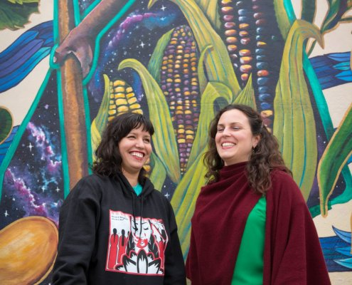 two artists stand smiling in front of a colorful mural