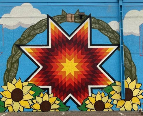 a colorful mural includes a star burst in the center surrounded by a cloudscape and sunflowers