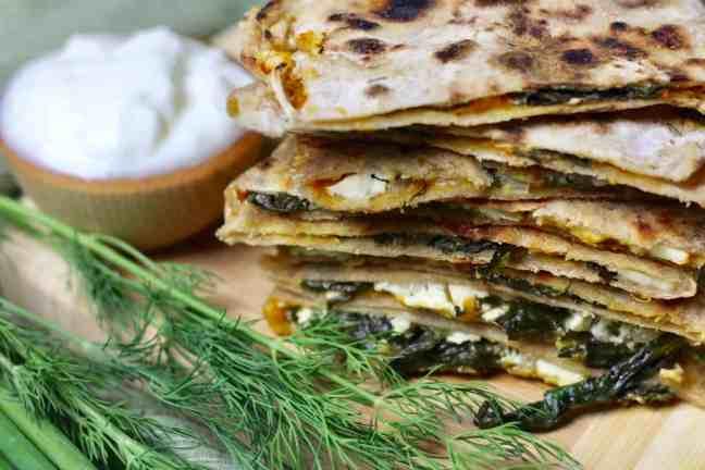 Stack of Qutab with herbs and yogurt dip