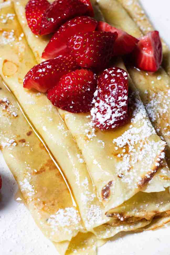 Close up of Palachinki with powdered sugar and strawberries