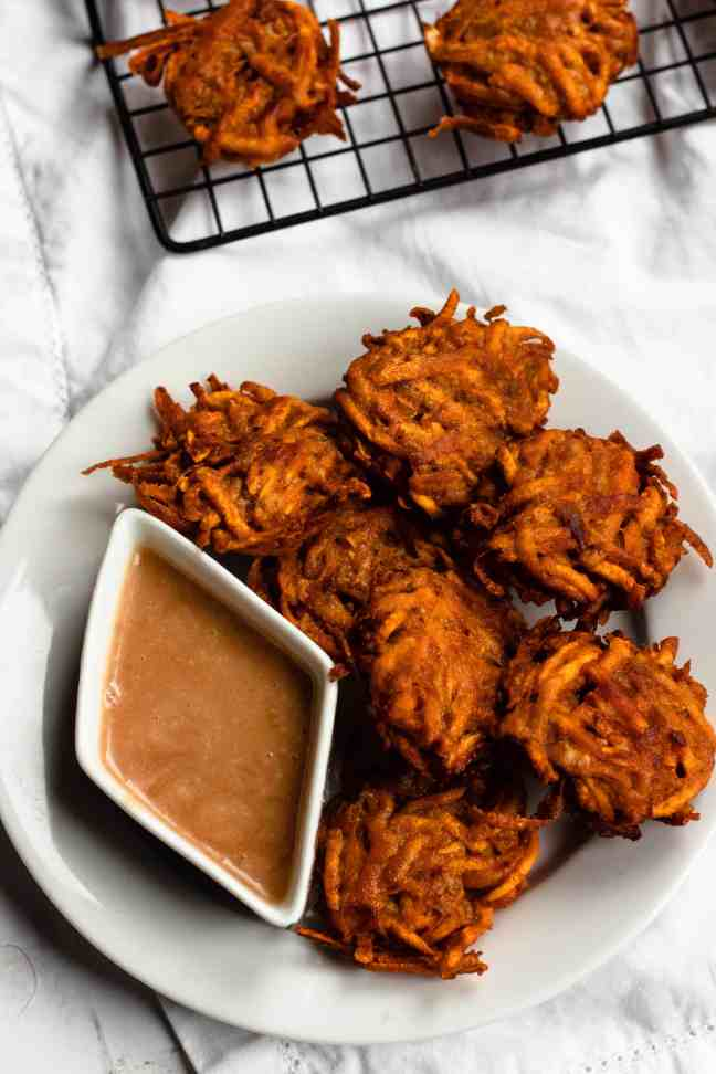 Plate of sweet potato fritters with a diamond-shaped container of lemon tahini sauce