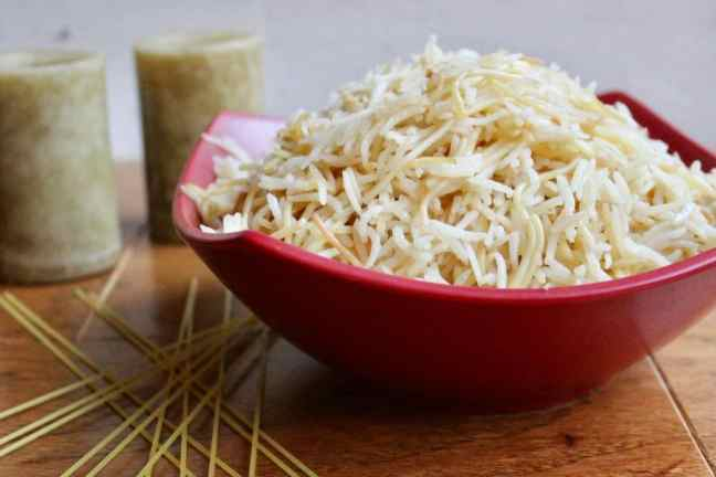 rice and vermicelli in a red bowl with candles