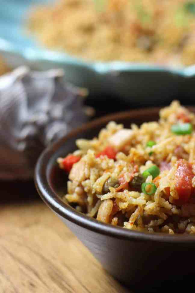 Pigeon peas and rice in brown bowl with shell in the background