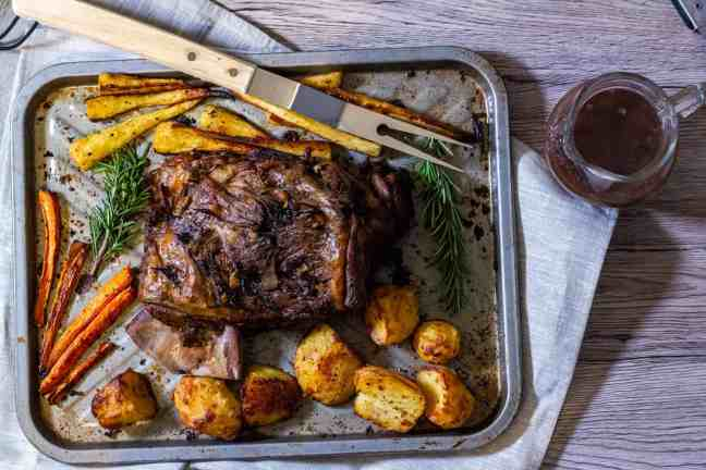 Slow cooked lamb on a baking sheet with vegetables and gravy on the side