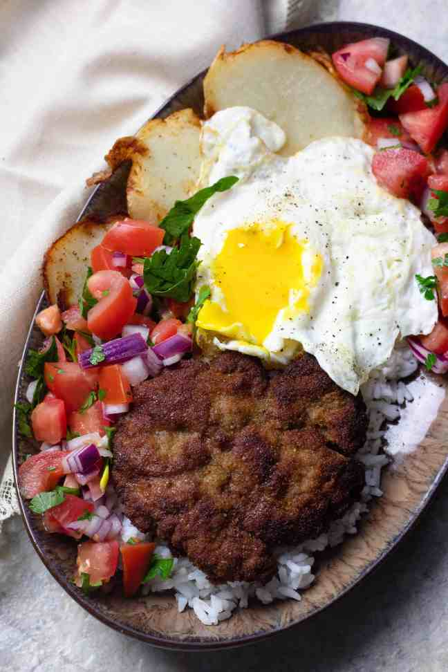 Silpancho with salsa and cracked over easy egg