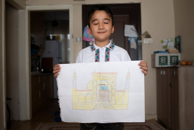 Ten-year-old Bilal Habibulla poses with his drawing of the Id Kah Mosque in Kashgar, Xinjiang, at his home in Istanbul on April 27. The Id Kah Mosque is a symbol for the Uighur culture.
