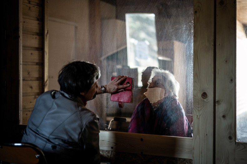 A woman shows her mother photos from her smartphone through a window at a retirement home in Roche-la-Molière, France, on April 15.