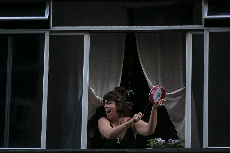 A protester bangs on a drum as she leans from her window to protest against Brazilian President Jair Bolsonaro in Rio de Janeiro on April 24.