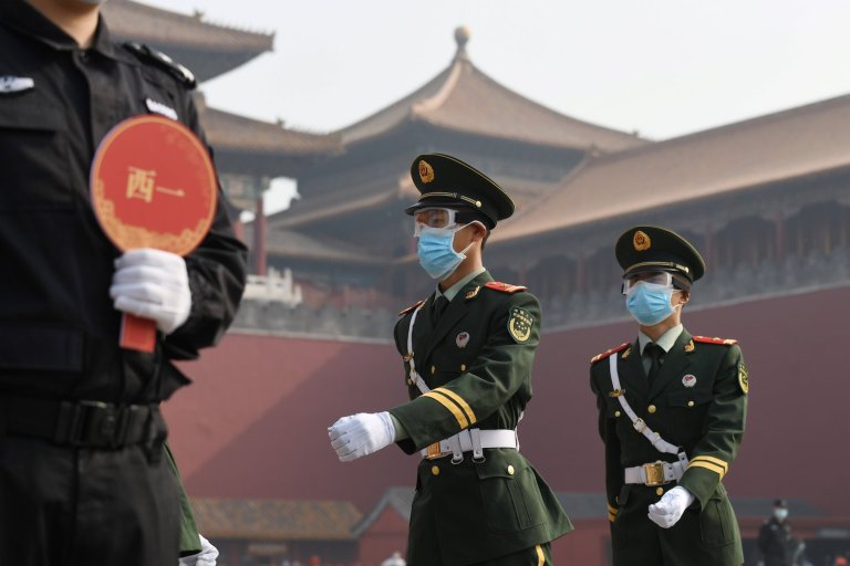 Paramilitary police officers wear face masks and goggles amid COVID-19 concerns as they march outside the Forbidden City, the former palace of China's emperors, in Beijing on May 1.