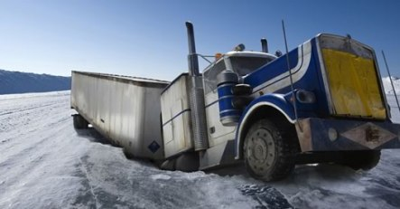 An ice road collapses beneath a truck.