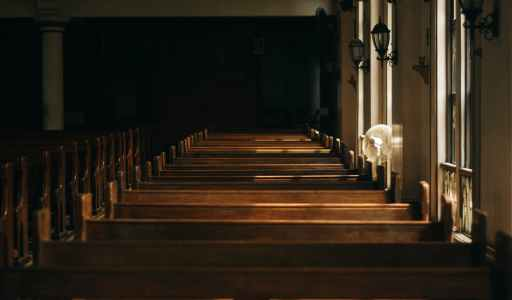 brown wooden church bench near white painted wall