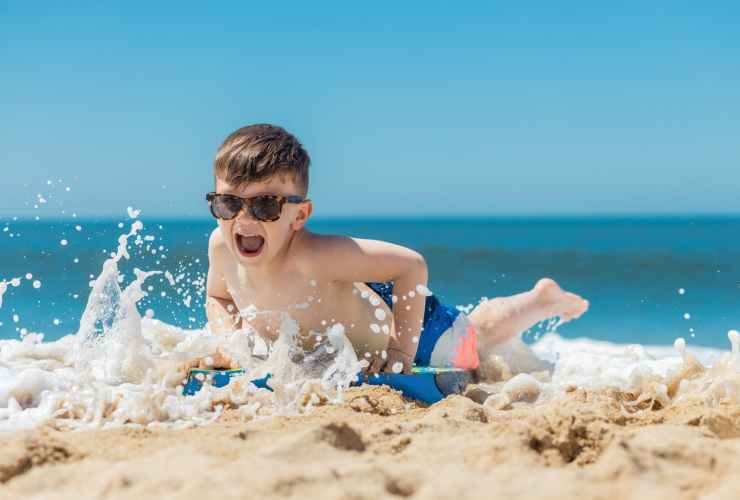 boy in blue swimming goggles on beach