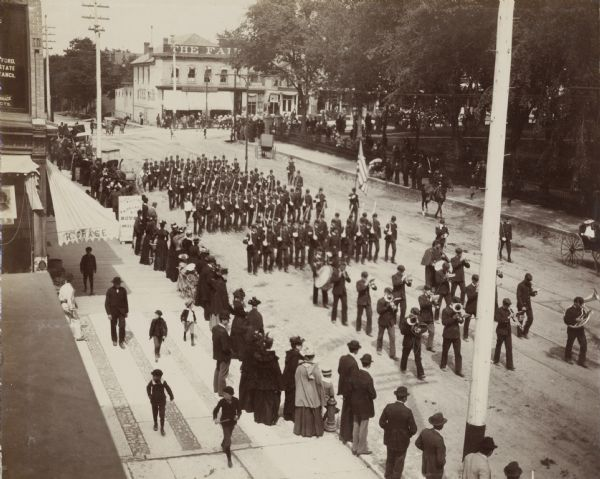 A military band and small group of soldiers march through Capital Park on Decoration Day in 1894.