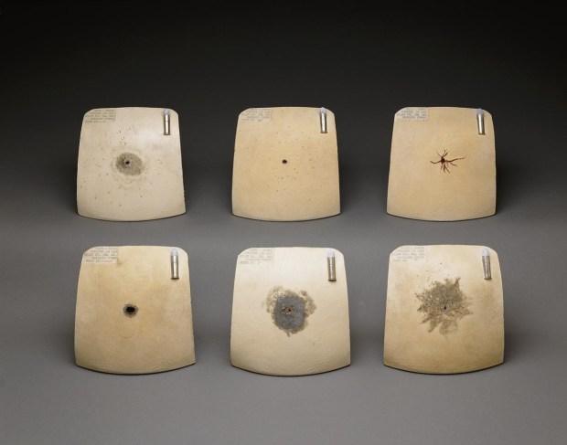 Gunshot patterns on six ceramic chest plates.