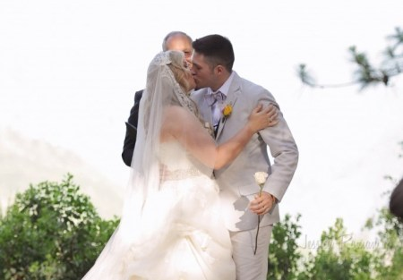 newlywed couple kiss the bride