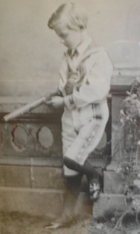 A photograph of Henry Douglas Freshfield as a young boy of about 8 years old. He is leaning against a low wall and seems to have something under his arm.