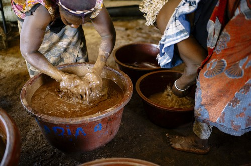 Once roasted, Rabo Nafissatou (left) and Bassia Mariam (right) ground the shea nuts to a paste, mix it with water and beat it, Burkina Faso.