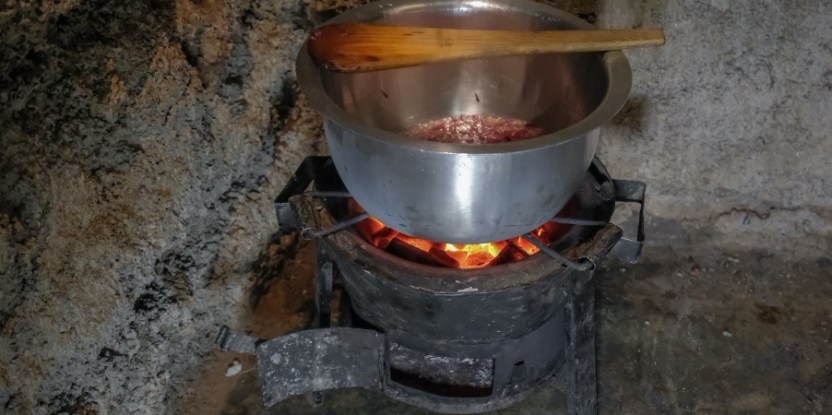 A pot sits on charcoal embers