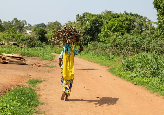 A woman walking along a dirt road with wood on her head