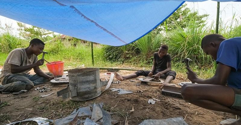 Men work on stove construction under under a tarpaulin