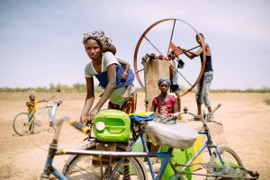 Barry Aliman, 24 years old, bicycles with her baby to fetch water for her family, Sorobouly village near Boromo, Burkina Faso. Climate change will affect rainfall patterns and the availability of water. Photo: Ollivier Girard/CIFOR