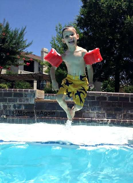 Happy child in air on his way down in pool.