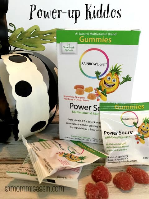 A box of Power Sours Multivitamins and packets and actually vitamin showing with polka dot black and white metal pumpkin off to the side. Rainbow Light