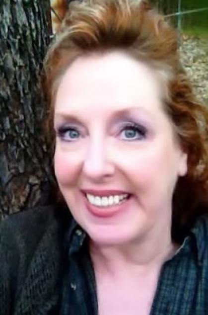 Red headed lady leaning next to a tree smiling big!!