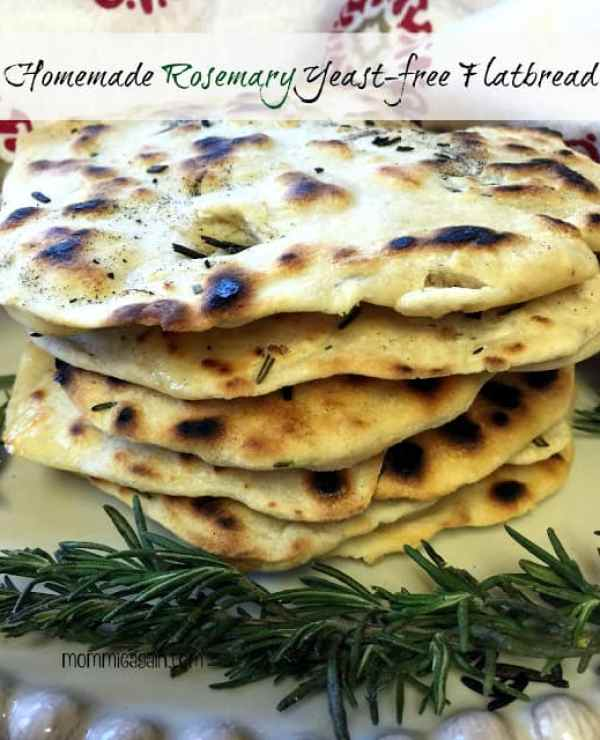 6 stacked homemade rosemary flatbread on plate with fresh rosemary from my garden (yeast-free_