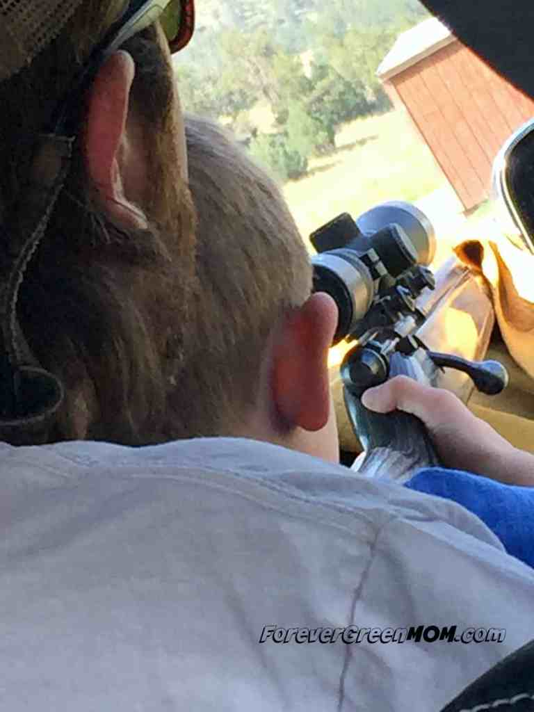 boy learning to shoot gun from man both riding in a truck