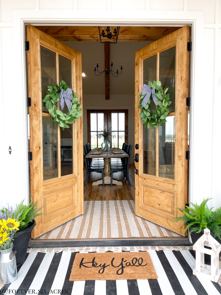 Farmhouse double doors leading into the dining room, that has a 10 ft long farmhouse table. This page goes over building a custom home.