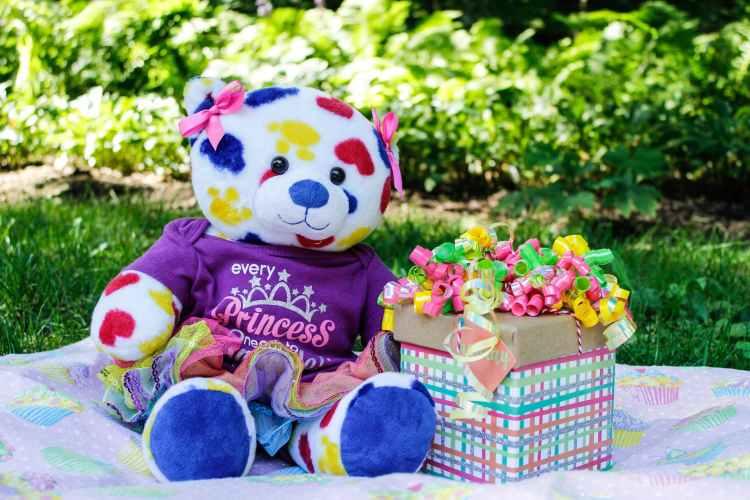 colorful teddy bear beside gift box