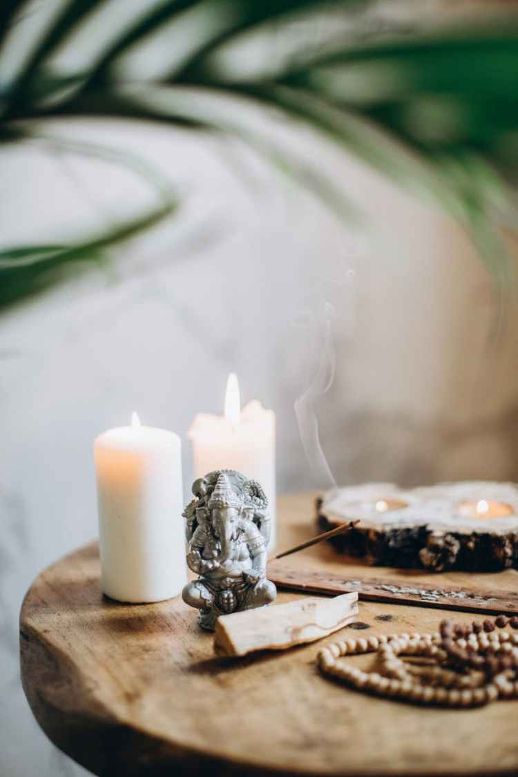 brown wooden table with candles and incense