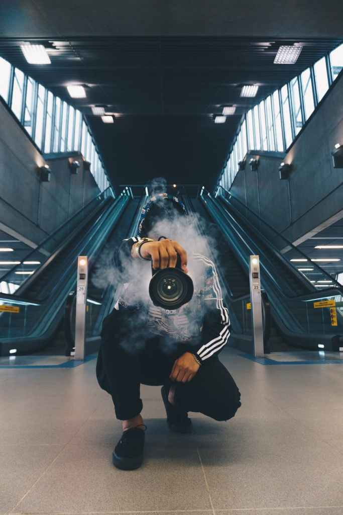 man holding camera while squating with smoke on face inside building