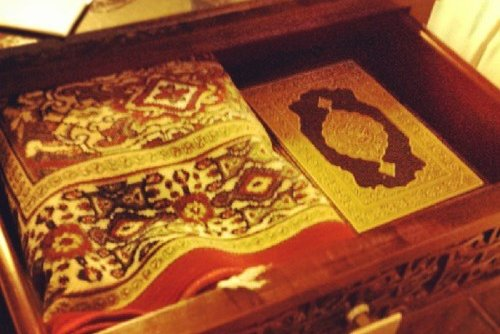 A Quran and a prayer rug in a wooden box