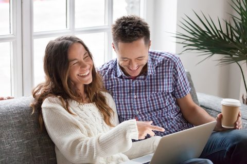 Two people on a couch laughing at computer