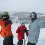 Three skiers on a ski slope
