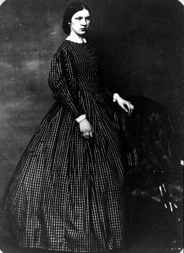 Louisa Fennell wearing a large dark coloured dress. She is looking off into the distance.