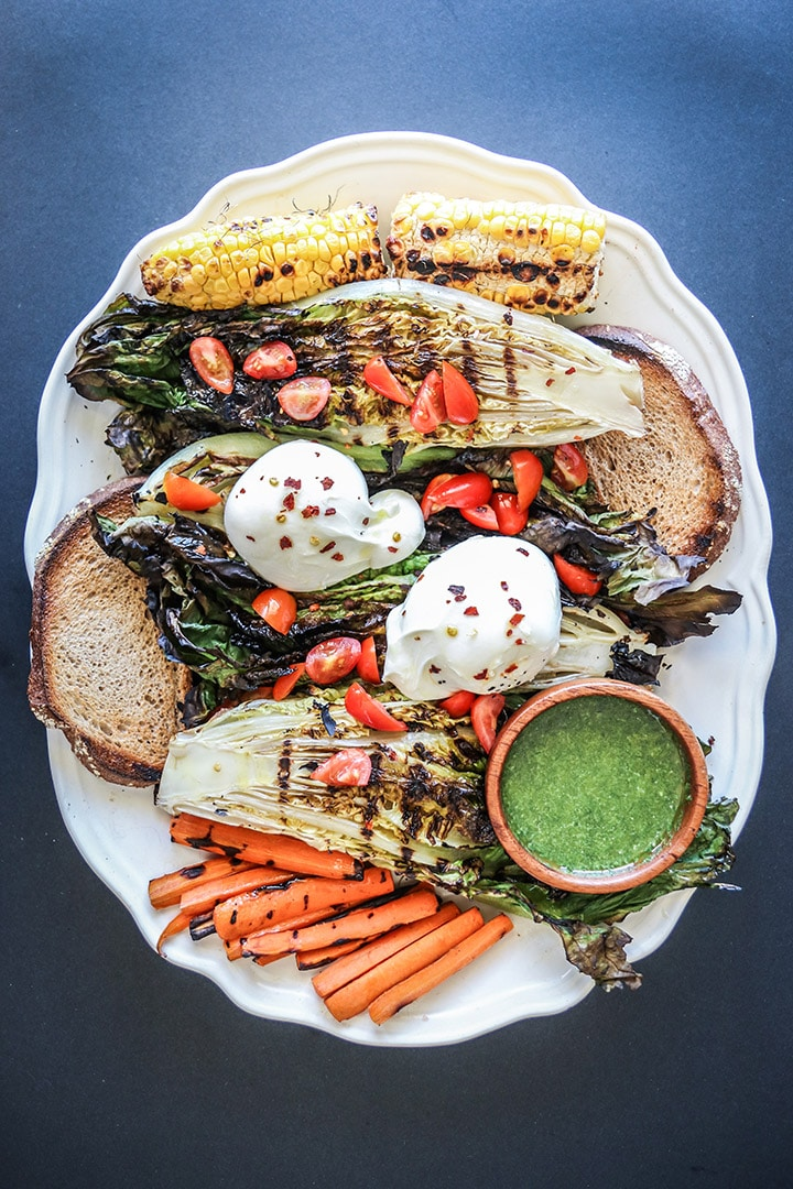 Grilled Romaine Burrata Salad, a platter of grilled heads of romaine topped with creamy burrata cheese, grilled summer vegetables and a garlic dill dressing drizzle. A perfect starter for summer barbecues!