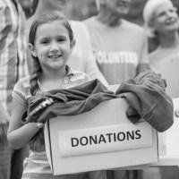 for kitty's sake child holding donation box