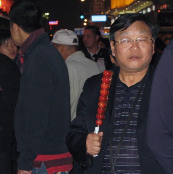 Beijing Night Market - man holding sugar coated plums