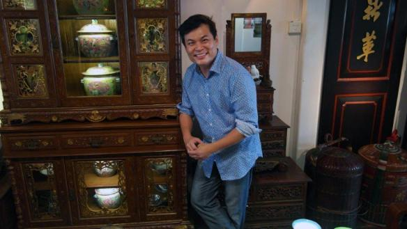 Alvin Yapp poses in front of a handsome dresser in Singapore-Dining capital of Asia