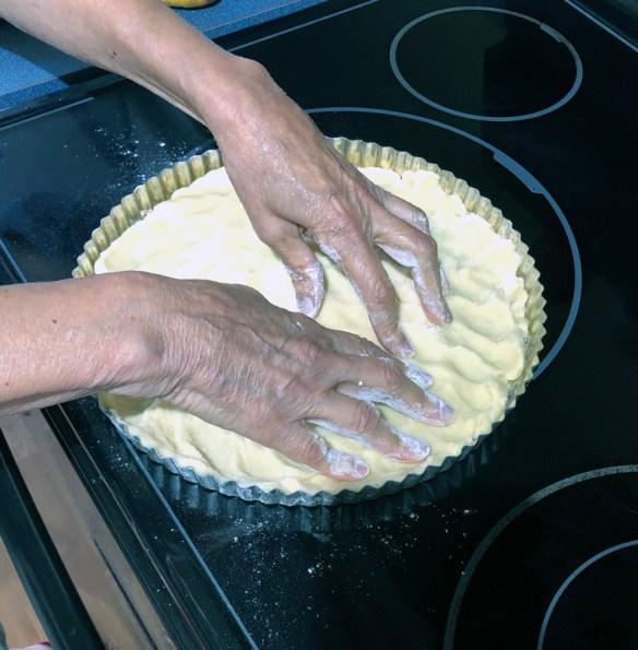 hands pressing dough into the edges. Fresh fruit tart