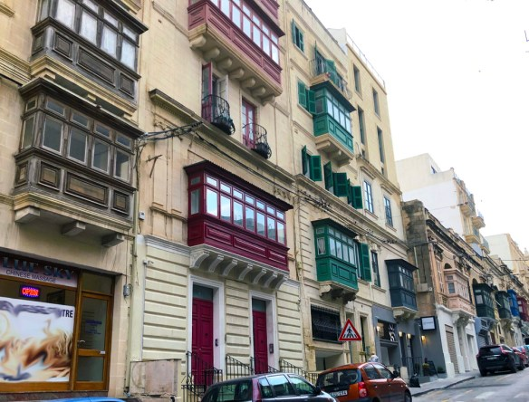 Houses with colourful, enclosed balconies jutting out.