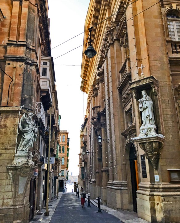 statues face each other in niches above street level on the corner
