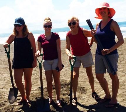 four women posing with shovels