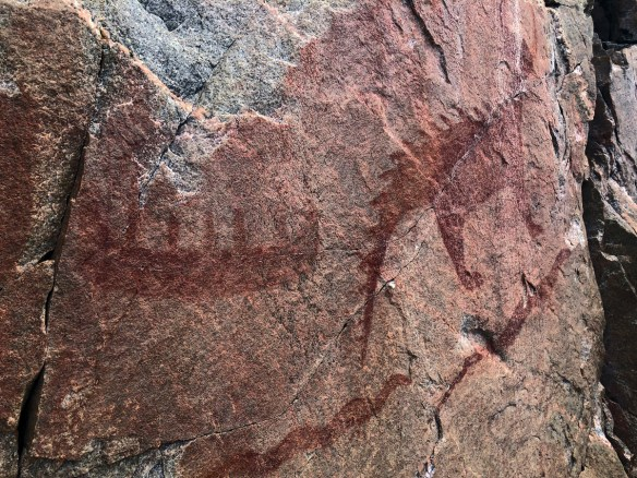 rock face with drawing of canoe and horned animal