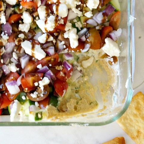 Make your own or use prepared hummus and you'll be the star of your next potluck with this Greek 7 Layer Dip! It's fresh, healthy and bursting with mediterranean flavors!