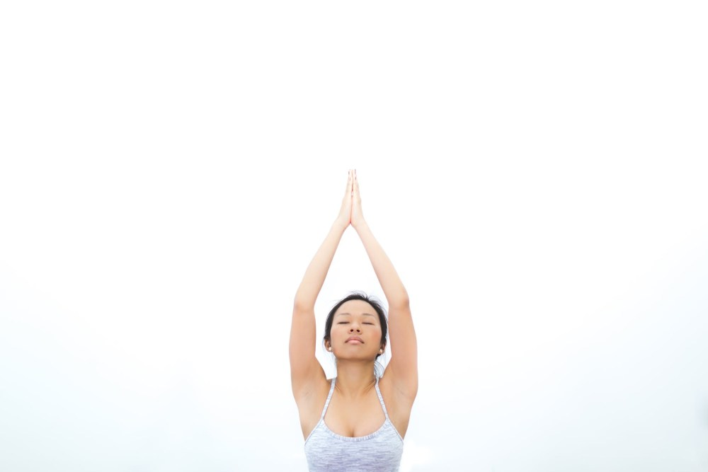 Woman practsing yoga in the workplace. Corporate wellbeing programmes UK.