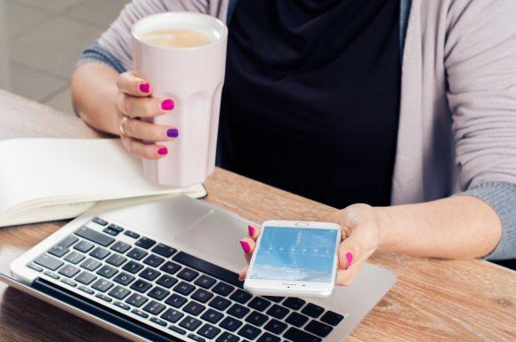 Une jeune femme consulte son smartphone devant son ordinateur portable et un bloc-note - outils de conception de formation en ligne